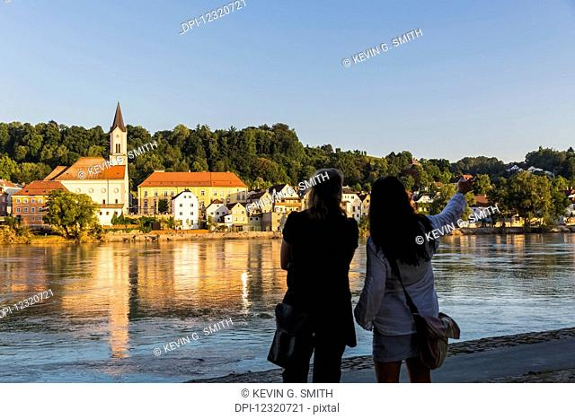 Water reflects the Saint Gertrud Church on the river Inn, with two women standing and looking away from the camera in the foreground pointing downriver; North...