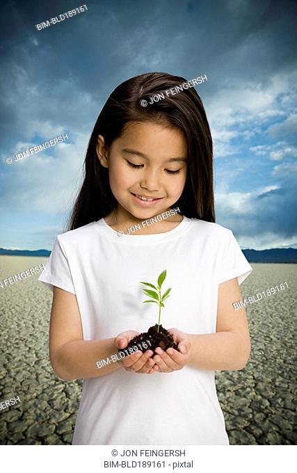 Chinese girl holding seedling in desert