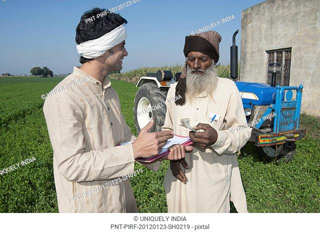 Farmer giving money to another farmer as agriculture loan, Sonipat, Haryana, India