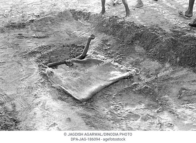 Beggar buried under sand only hands showing Chowpatty Mumbai India Asia 1974