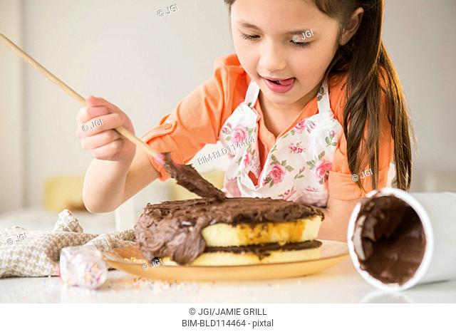 Mixed race girl icing cake in kitchen