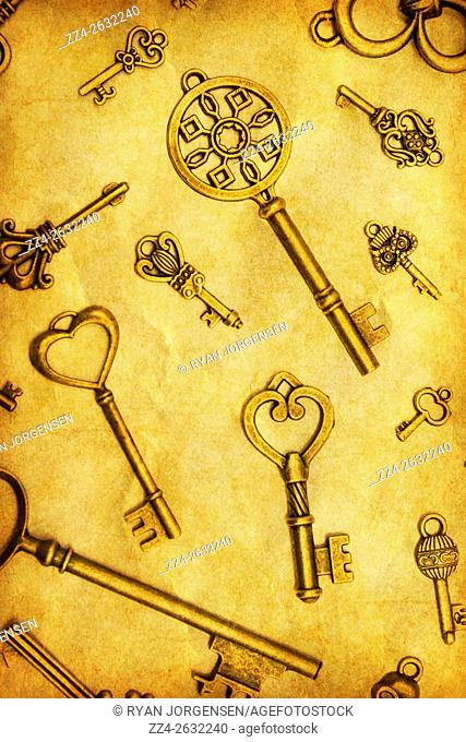Close-up of vintage metal keys of different size and form on yellow background. Yellow toned. From above