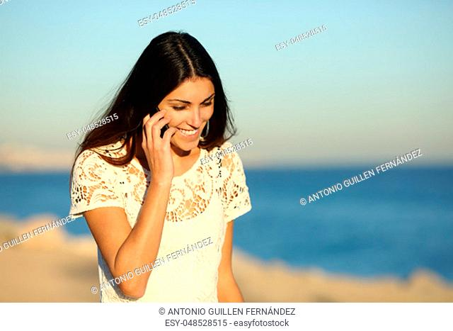 Happy woman talking on phone walking on the beach in a sunny day