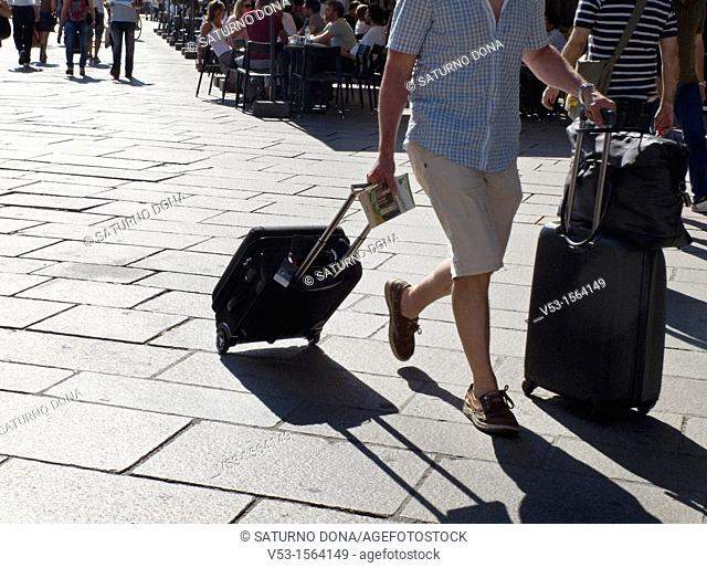 Person in crowd pulling trolley luggage case on street, Milan, Italy, Europe