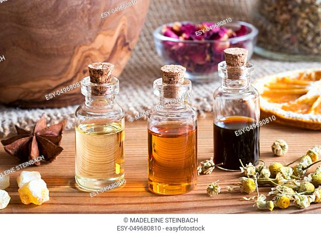 Bottles of essential oil with star anise, frankincense, dried chamomile flowers and dried orange slices