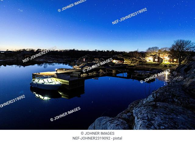 Lake with pier and speed boat at night