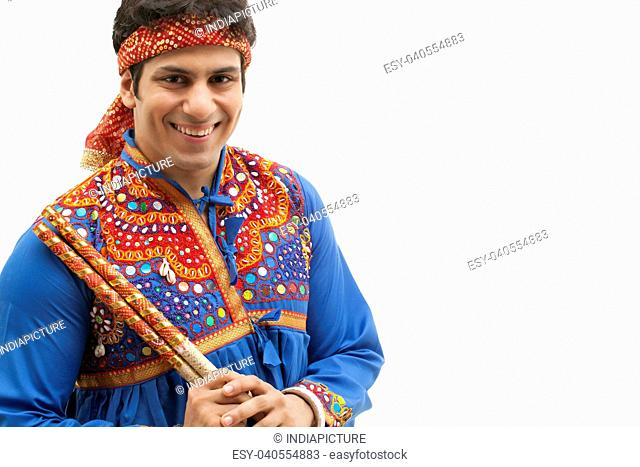Portrait of happy young man in traditional wear holding dandiya isolated over white background