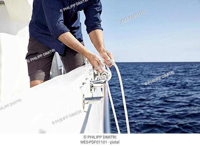 Man on motor yacht tying a knot, partial view