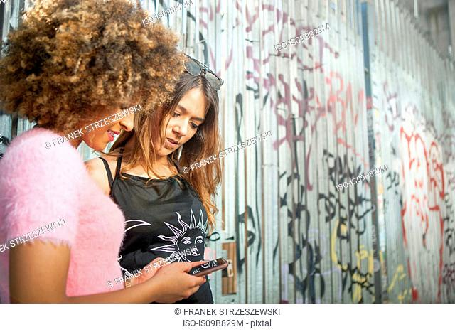 Two young women in street, looking at smartphone