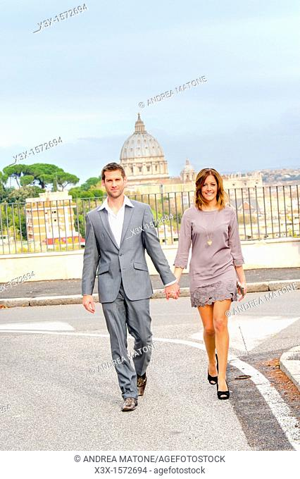 Couple crossing the street in front of Saint Peter's dome in Rome Italy