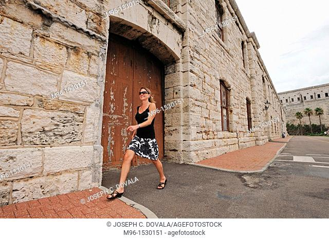Woman walking along old buildings at the Dockyard, Bermuda Island, Atlantic