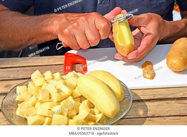 Man's hands, peeling potato