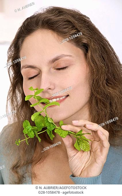 young woman breathing a sprig of fresh mint