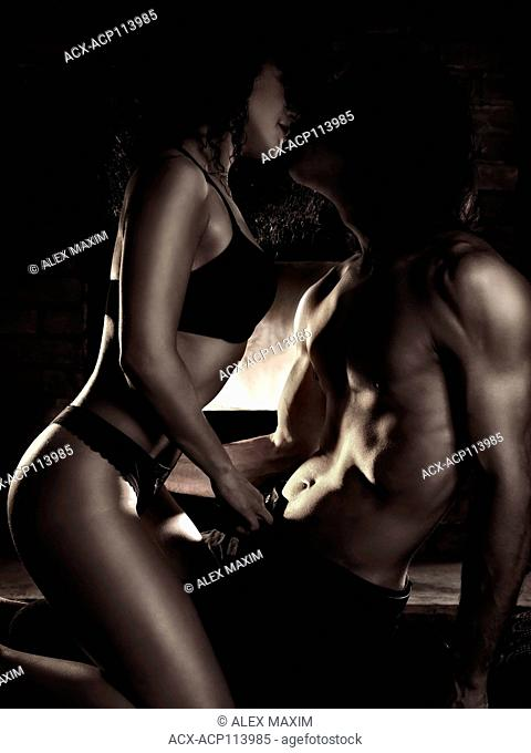 Sensual artistic photo of a sexy young kissing couple making love in front of a fireplace