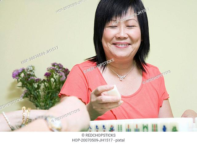 Close-up of a mature woman playing mahjong and smiling