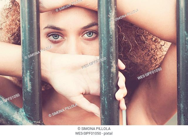 Young woman behind bars