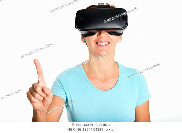 Woman looking in VR glasses and gesturing with his hands. Beautiful surprised female wearing virtual reality goggles watching movies or playing video games