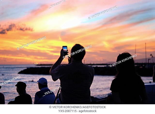 Tourist taking picture of a spectacular sunset at Waikiki beach in Honolulu, Hawaii