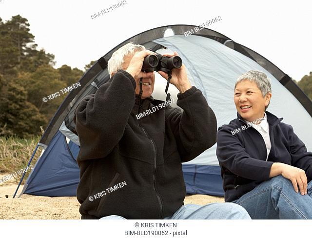 Senior Asian couple camping with binoculars