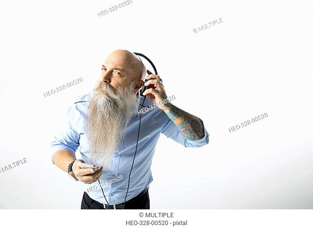 Portrait hipster businessman with beard listening to music with headphones against white background