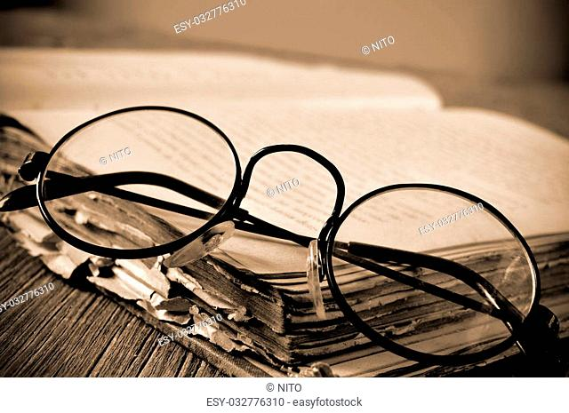 a pair of round-framed eyeglasses on an old book, on a rustic wooden table, in sepia toning and slight vignette added