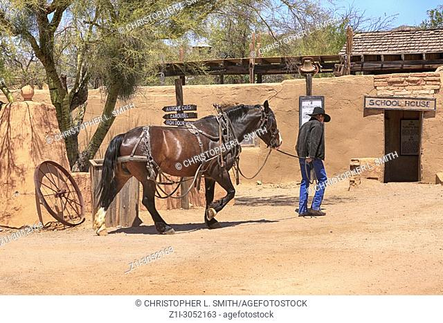 Old Cowboy leading his horse to the stable building at the Old Tucson Film Studios amusement park in Arizona