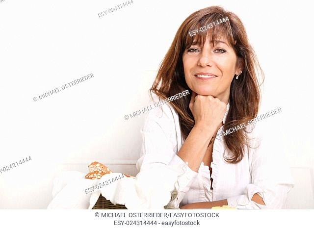 Portrait of a beautiful mature woman sitting in the kitchen