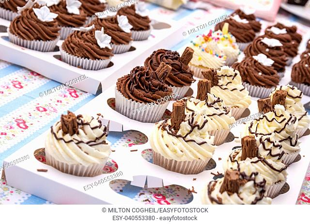 An assortment of homemade chocolate and vanilla cupcakes with a chocolate flake