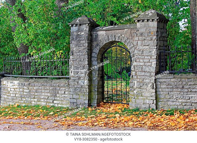 Old stone wall and iron gate on a day of autumn. Helsinki, Finland