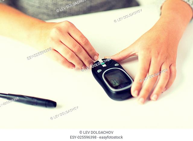 medicine, diabetes, glycemia, health care and people concept - close up of woman hands with glucometer and test stripe checking blood sugar level at home