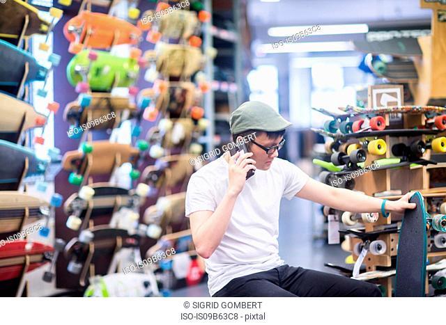 Young male skateboarder making smartphone call in skateboard shop