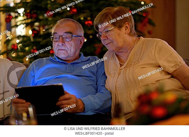 Senior couple looking at digital tablet in front of Christmas tree