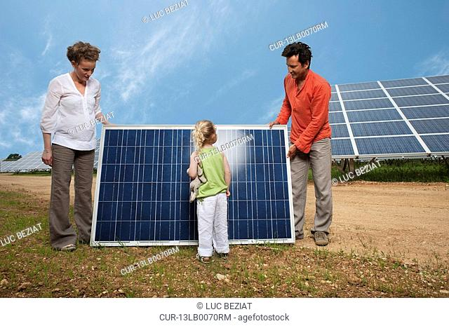 family in front of solar panel