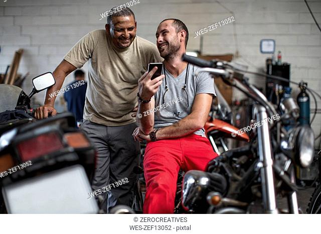 Two smiling mechanics in motorcycle workshop looking at cell phone