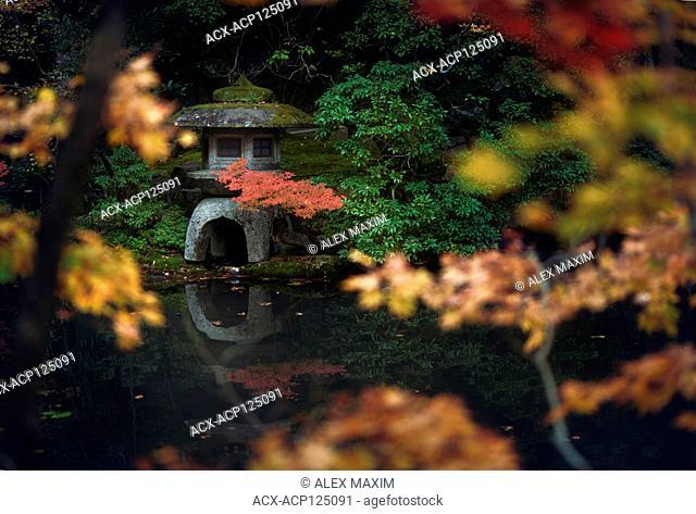 Japanese stone lantern, Ishidoro reflecting in the water of a pond of Tenju-an Temple garden. Nanzen-ji temple complex in Sakyo-ku, Kyoto, Japan 2017