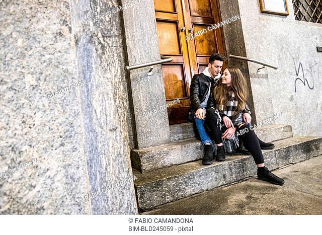 Caucasian couple sitting on concrete front stoop