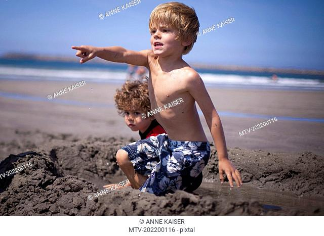 Little boy showing something to his brother on the beach, Viana do Castelo, Norte Region, Portugal