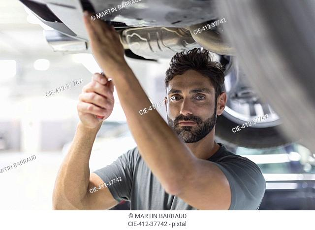 Portrait serious male mechanic working under car in auto repair shop