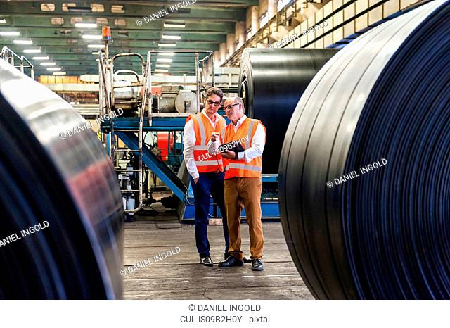 Two male workers having discussion in rubber roller factory