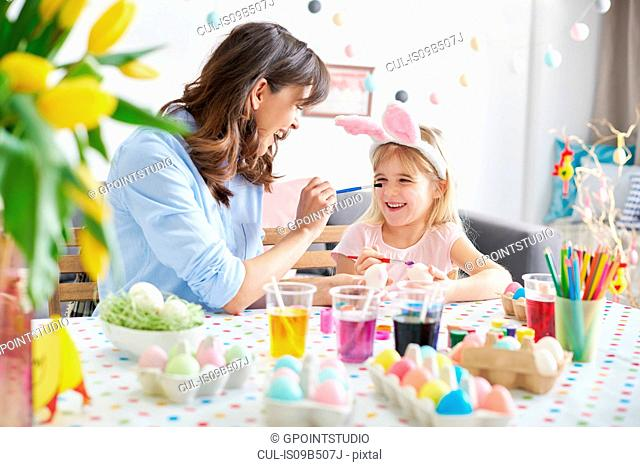 Woman painting daughter's nose while painting easter eggs at table