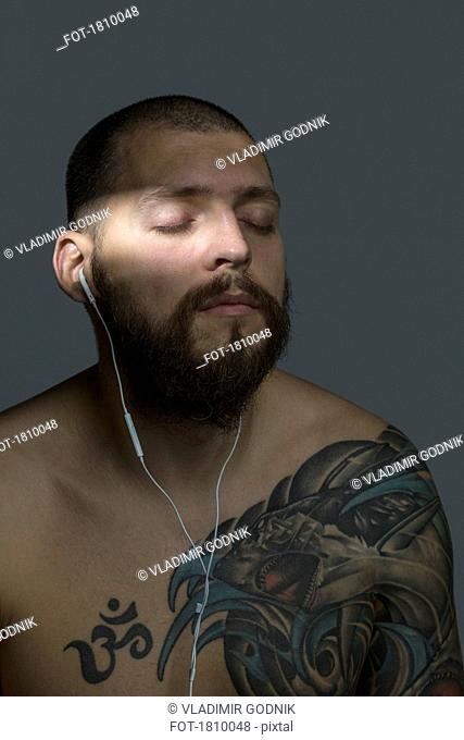 Serene bare chested man with beard and tattoos listening to music with earbuds