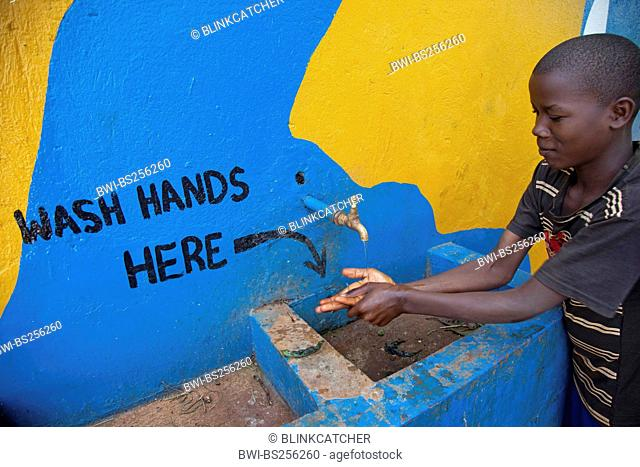 boy is washing his hands at a tap, the painted words on the wall say 'wash hands here', Uganda, Jinja