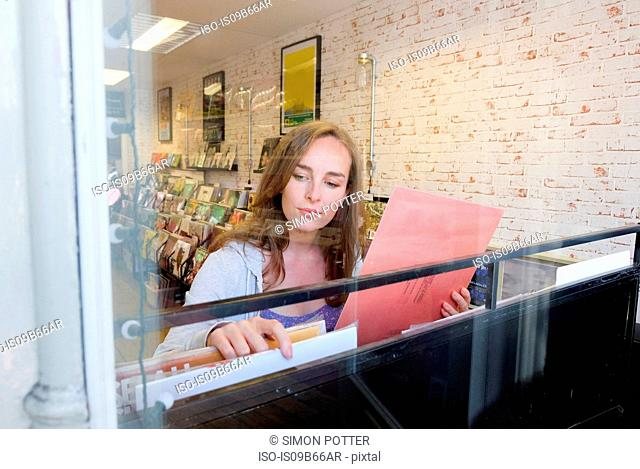 Young woman looking at vinyl records in record store