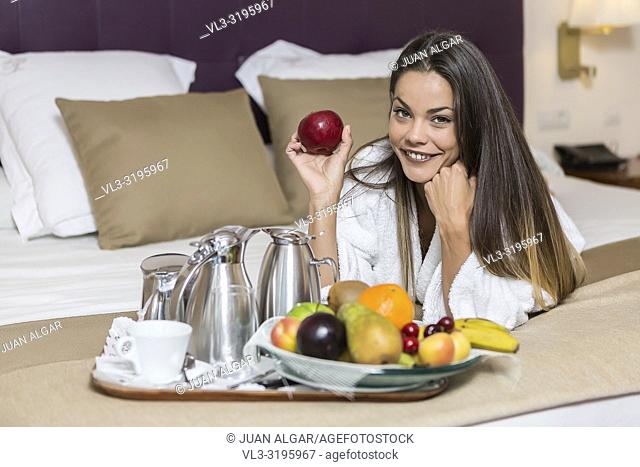 Pretty brunette woman lying on bed of hotel room in white morning gown near plate full of fruits and holding apple