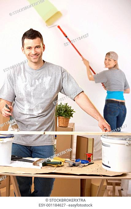 Cheerful couple painting their home