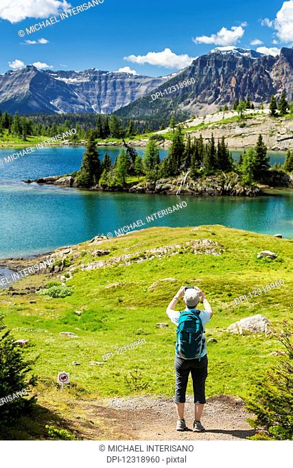 Female hiker standing on a trail taking a photo with her phone of an alpine lake with mountains, blue sky and clouds; Banff, Alberta, Canada