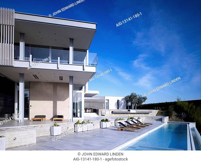 Modern detached house, West Hollywood, California. Rear general view with infinity pool and sun loungers