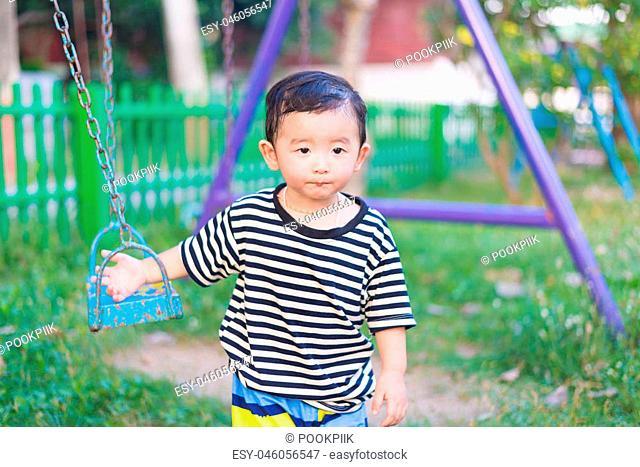 Sad little Asian kid at the playground under the sunlight in summer, Kids play on school yard. shallow DOF