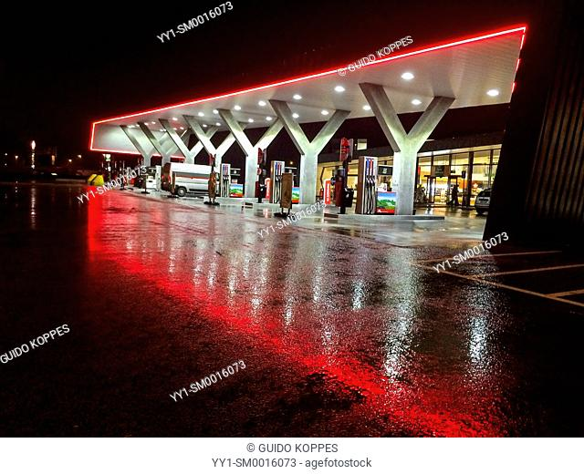E40 Highway, Belgium. Cars, vans an vehicles getting fueled up at a nightly gasstation alongside the highway