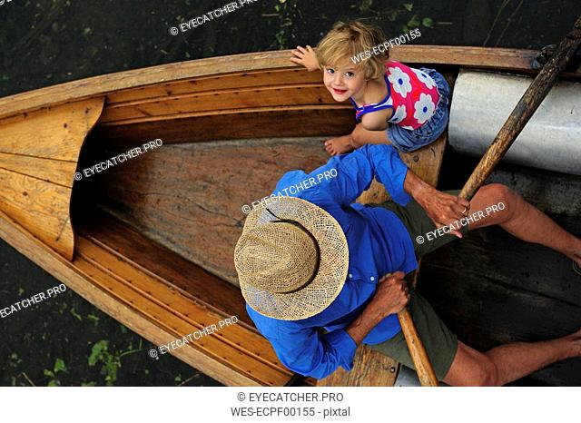 Happy little girl with her grandfather in rowing boat, top view
